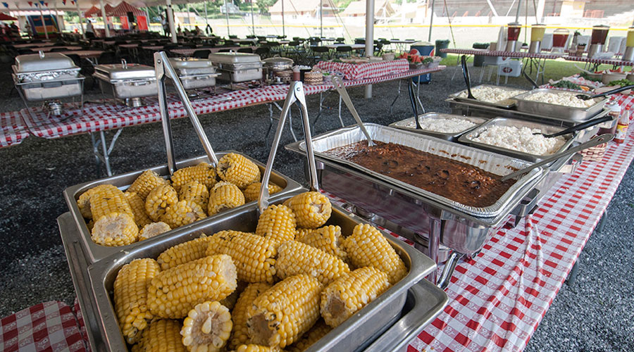 catering setup of corn, beans, salads and fruit