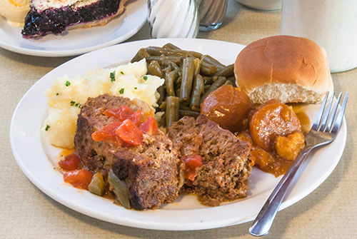 dinner plate of meatloaf with roll, vegetables, pie and coffee