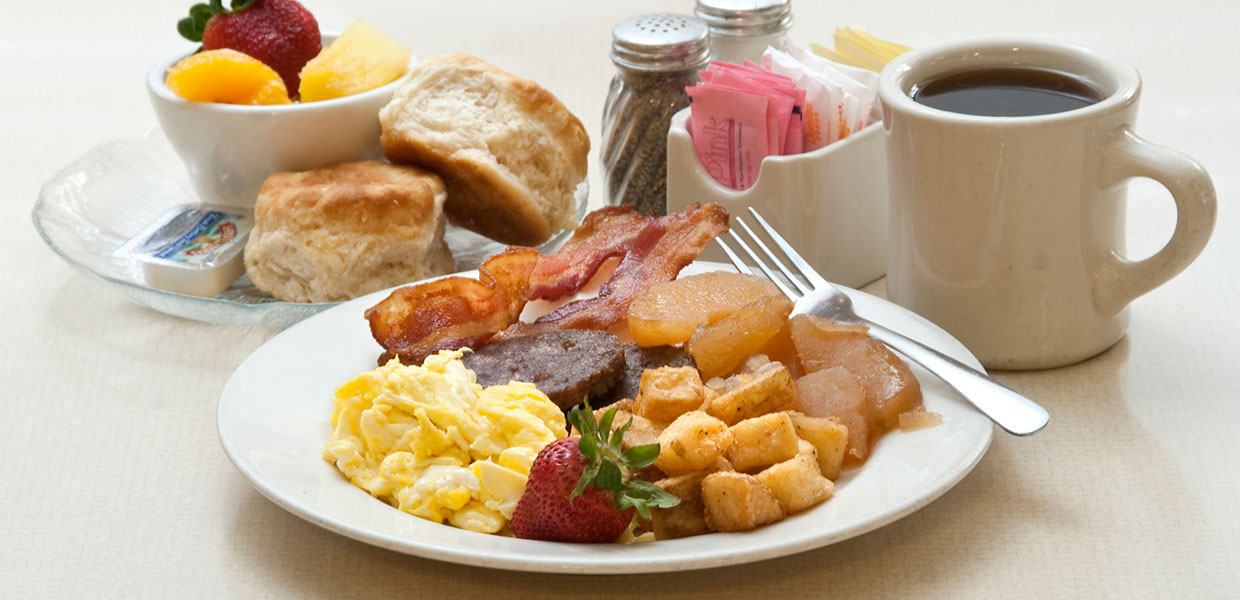 breakfast plate with potatoes, fruit, sausage, eggs, bacon and biscuits