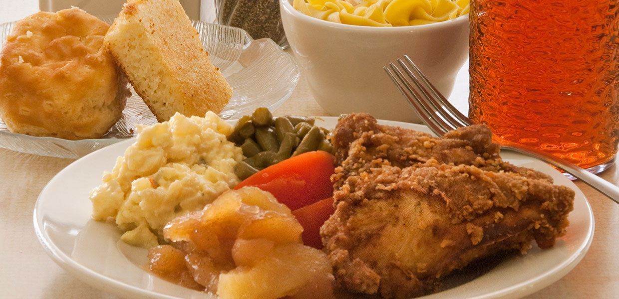 dinner plate with fried chicken, vegetables, fruit, cornbread and ice tea